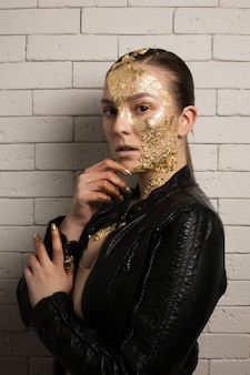 Fashion shot of elegant brunette woman with gold foil on her face and neck, wearing leather jacket