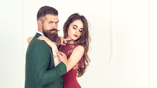 ファッションショット。美しいセクシーな女性のポーズでスーツを着たハンサムなエレガントな男のファッション写真。エレガントなイブニングドレスの性的な情熱的なカップル。男性の腕の中で救われていると感じている女性。豪華なインテリア