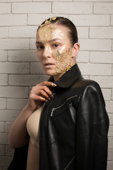 Fashion shot of gorgeous brunette woman with gold foil on her face and neck, wearing leather jacket