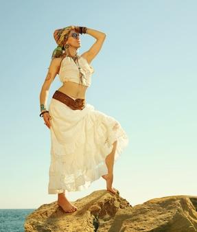 바다 근처 바위에 서있는 아름 다운 boho 스타일 여자의 패션 샷. boho 의상, 히피, 인디 스타일