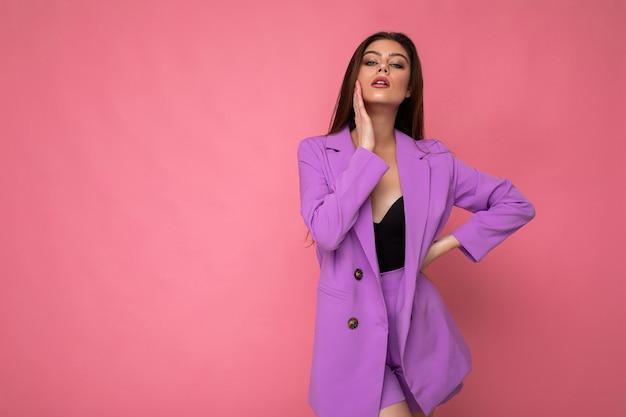 Съемка моды молодой сексуальной счастливой привлекательной женщины брюнет, носящей стильный фиолетовый костюм, изолированную на розовом фоне с пустым пространством. бизнес-концепция