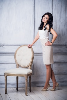 Fashion shot of young beautiful woman in white short dress standing near antique chair in front of luxury white wall with decorative mouldings