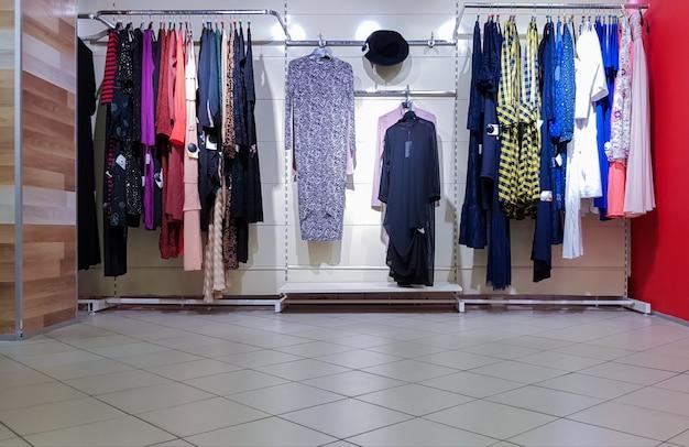 옷걸이에 매장 내부의 세련되고 세련된 고급스러운 옷의 패션쇼. 편집 사진. 쇼핑은 소녀와 여성이 가장 좋아하는 휴가입니다.