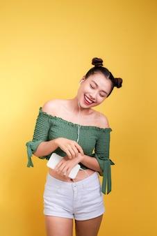 Модная улыбающаяся азиатская женщина, слушающая музыку в наушниках на желтом фоне