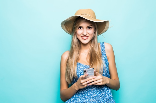Fashion smiling woman is using smartphone wearing straw hat on blue background