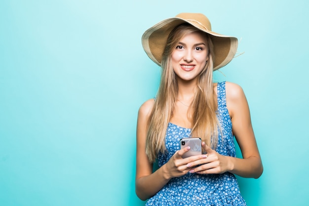 ファッション笑顔の女性は青い背景に麦わら帽子をかぶってスマートフォンを使用しています