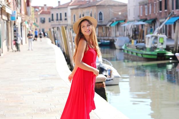ファッション。イタリア、ベニスのムラーノの旧市街を歩いて振り返る笑顔の若いスタイリッシュな女性。