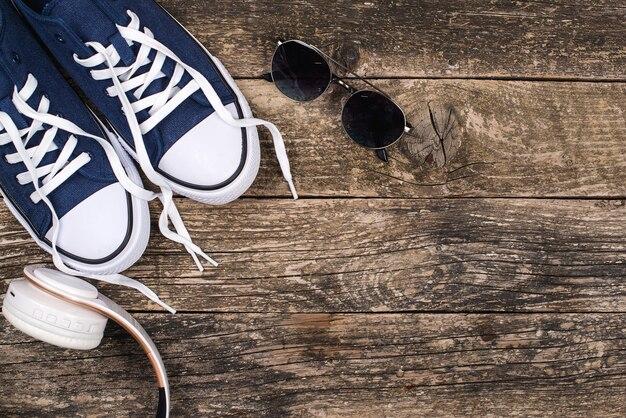 Модные кроссовки, солнцезащитные очки и современные беспроводные наушники. мужская мода. скопируйте пространство.