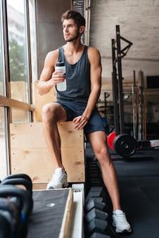 Fashion sportsman in gym. with bottle