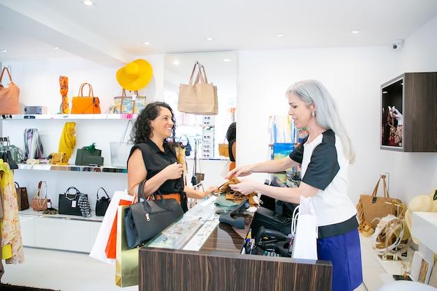 Кассир магазина модной одежды складывает одежду новых клиентов для упаковки и беседует с покупателем. вид сбоку. покупки или концепция покупки