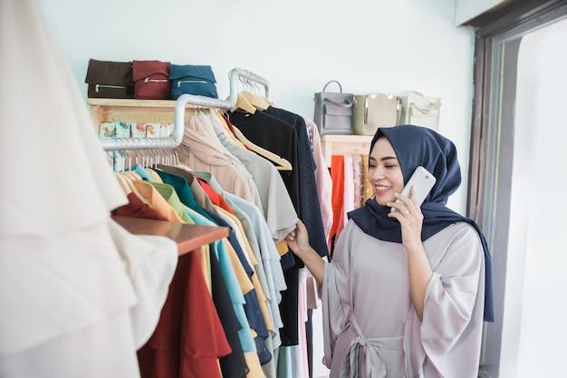 Покупатель модного магазина разговаривает по телефону при совершении покупок