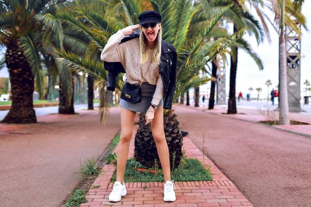 Immagine di strada di moda della modella con gambe lunghe che indossa abiti eleganti e glamour, primavera, atmosfera di viaggio, palme intorno, scarpe da ginnastica, berretto, giacca di pelle, minigonna, maglione, accessori e gioielli.