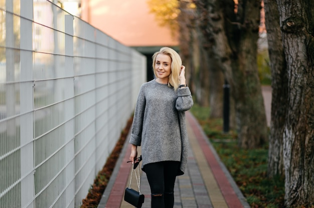 Fashion street photo session of stylish young lady in a grey clothes
