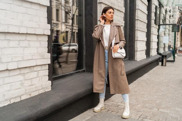 Moda ritratto di strada di elegante donna bruna europea in cappotto di pelle in posa all'aperto