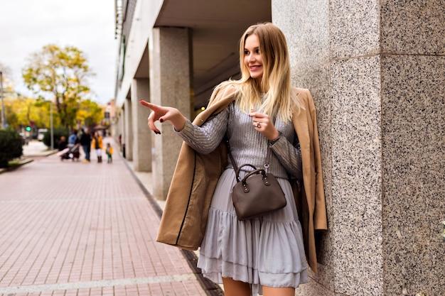金髪のエレガントな女性のファッションストリートスタイルの写真。豪華なシルクのドレス、トレンディなセーター、カシミアコート、革のバッグ、柔らかな暖色、春秋のミッドシーズン気分を身に着けています。