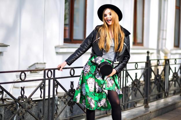 Модный уличный портрет красивой женщины с удивительными длинными светлыми волосами, стильной милой одеждой, длинной винтажной юбкой, элегантной шляпой и байкерской курткой, центром европейского города, стильной путешественницей, моделью.