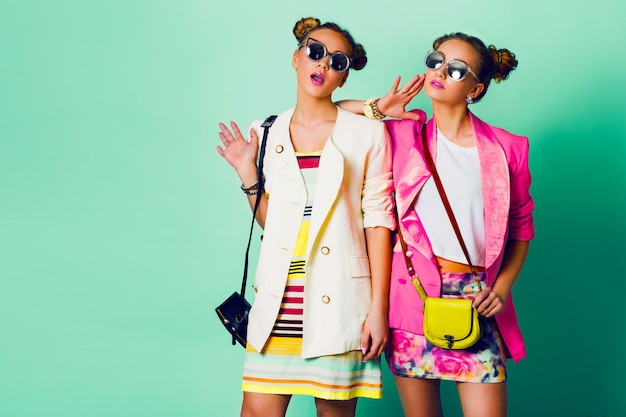Fashion studio image of two young women in stylish casual  spring outfit   having fun, show  tongue. bright trendy   colors, stylish hairstyle  with buns , cool sunglasses. friends portrait.