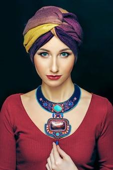 豪華なネックレスの帽子と明るいメイクでゴージャスな女性のファッションスタジオ写真