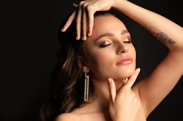 プロのメイクとスタジオで裸の肩を持つ美しいブルネットの女性のファッションスタジオの肖像画。テキスト用のスペース