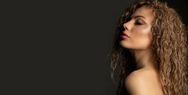 緑豊かな髪と裸の肩を持つ素晴らしいブロンドの女性のファッションスタジオの肖像画。コピースペース