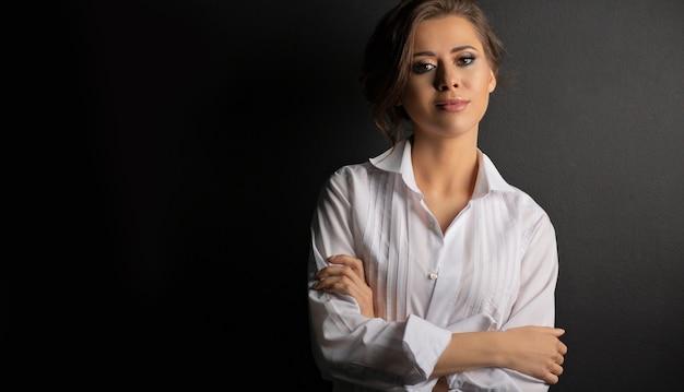 愛らしい若い女性のファッションスタジオの肖像画は、スタジオで白い男性のシャツを着ています。テキスト用のスペース