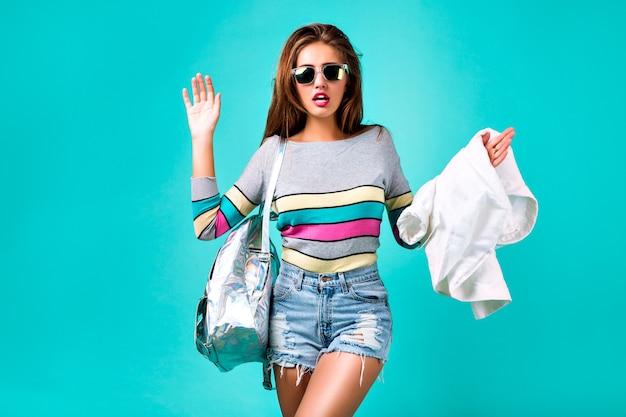 グラマースポーツ少女、スマートカジュアルな服装、かわいい感情、スタイリッシュな流行に敏感な服のサングラス、バックパック、春のパステルカラーのファッションスタジオポートレート。ミニヒップスターデニムショートクレイジーな感情。