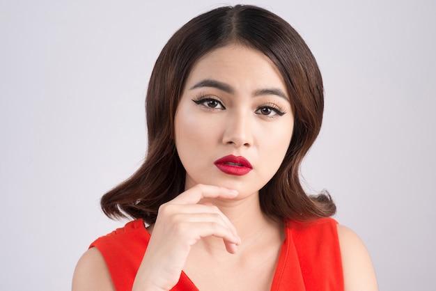 黒髪のゴージャスな官能的なアジアの女性のファッションスタジオの肖像画は、エレガントな赤いドレスを着ています