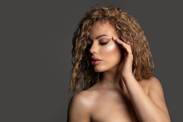 緑豊かな髪と裸の肩を持つセクシーなブロンドの女性のファッションスタジオの肖像画。空きスペース