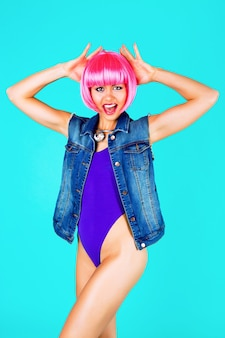 Fashion studio portrait of pretty woman wearing pink party wig bright make up and swag style outfit