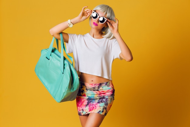 ファッションスタジオポートレート珍しいかなりブロンドの女の子の短いパーティーのかつら、白いトップとセクシーなスカートが黄色の背景に屋内でポーズします。日当たりの良い肯定的な感情、スタイリッシュなサングラス。