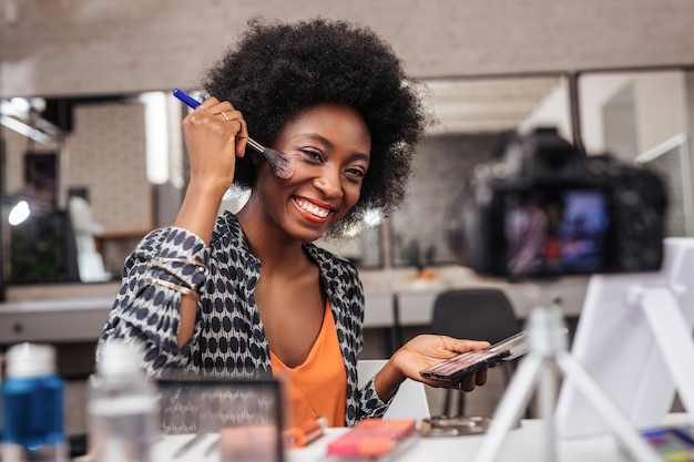 In the fashion studio. positive dark-skinned woman with curly hair giving a video lesson while sitting