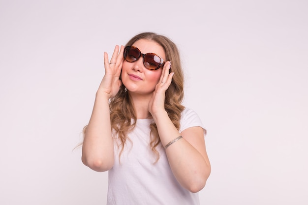 패션, 스타일과 사람들 개념-흰색 표면 위에 선글라스를 착용하는 매력적인 젊은 여자