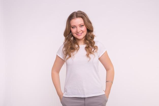 Концепция моды, стиля и людей - довольно молодая женщина, одетая в белую рубашку на белом фоне