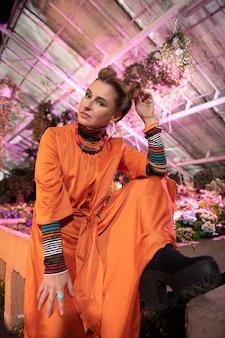 ファッションスタイル。オレンジ色のドレスを着てポーズをとりながら髪に触れて喜んでいるハンサムな女性