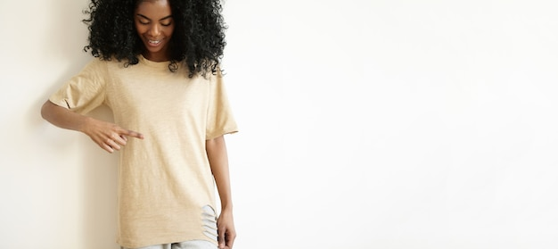 Fashion, style, design and clothing concept. cropped shot of good-looking young african woman with afro haircut wearing stylish ripped oversize t-shirt, pointing finger at it and smiling joyfully