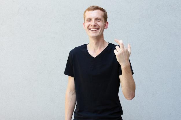 ファッション、スタイル、感情、人々のコンセプト-灰色の背景の黒いtシャツにそばかすのある美しい男らしい男の赤毛の肖像画を閉じます。幸運と笑いのために彼の指を交差させた