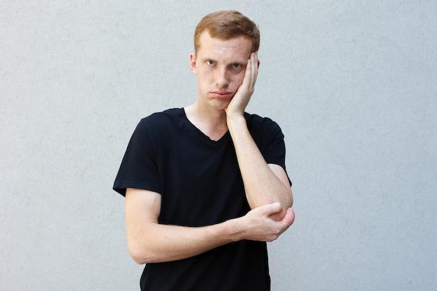 ファッション、スタイル、感情、人々のコンセプト-灰色の背景の黒いtシャツにそばかすのある美しい男らしい男の赤毛の肖像画を閉じます。疲れた手で頭を抱える
