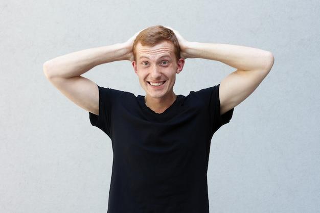 ファッション、スタイル、感情、人々のコンセプト-灰色の背景の黒いtシャツにそばかすのある美しい男らしい男の赤毛の肖像画を閉じます。頭を抱えて笑う