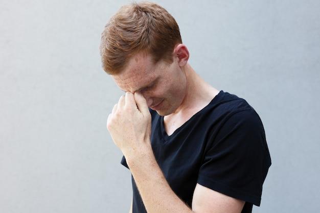 패션, 스타일, 감정과 사람들 개념-회색 배경에 검은 색 티셔츠에 주근깨가있는 아름다운 남자 다운 남자의 빨간 머리의 초상화를 닫습니다. 남자는 슬프다