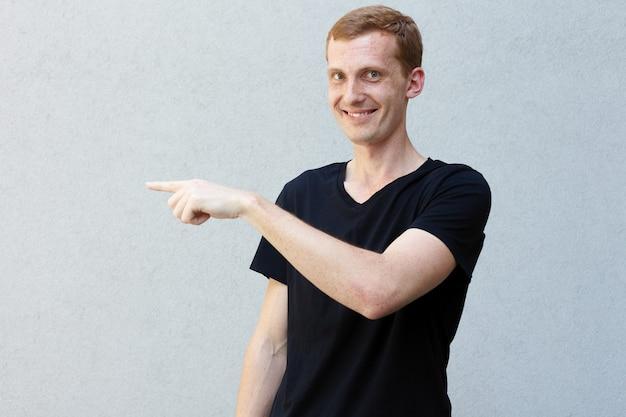 Концепция моды, стиля, эмоций и людей - крупным планом портрет рыжего красивого мужественного парня с веснушками на серой предпосылке черной футболке. указывая в сторону указательными пальцами