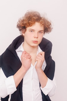 Fashion, style, people concept - portrait of young tender redhead teenage man with healthy freckled skin wearing white top looking at camera with serious or pensive expression.