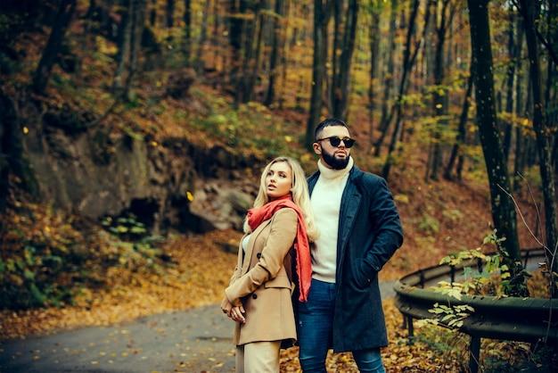 秋の背景に美しいカップルのファッションスタイルの写真