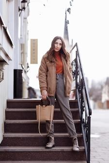 ファッションスタイルの肖像画。髪の長い美しいスタイリッシュな女の子が街を歩きます。路上で魅力的な女の子の肖像画。春または秋の日。セレクティブフォーカス。