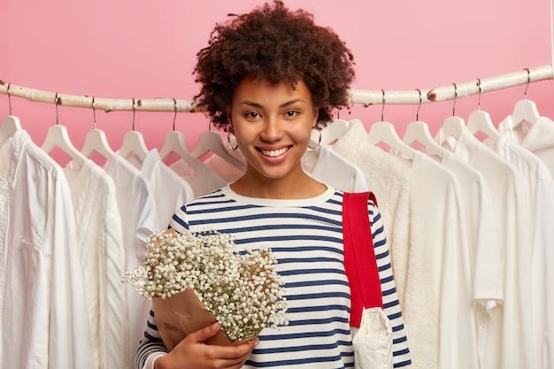 Moda, stile e concetto di acquisto. il cliente positivo della giovane donna posa alla mostra vicino ai vestiti bianchi come la neve sui ganci, sceglie il nuovo indumento per un'occasione speciale