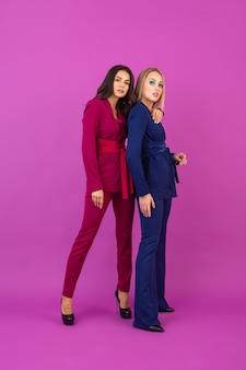 Модный стиль две улыбающиеся привлекательные женщины на фиолетовой стене в стильных красочных вечерних костюмах фиолетового и синего цвета, весенняя модная тенденция