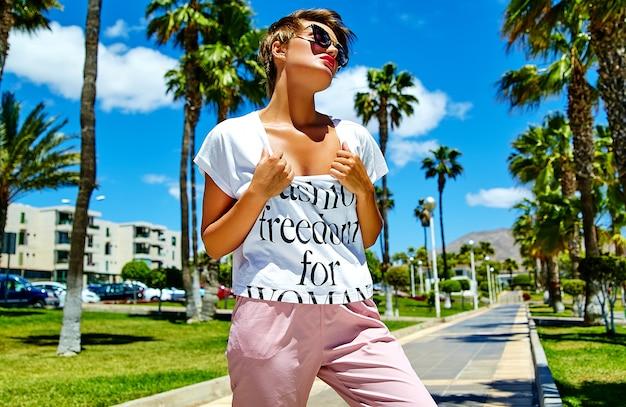 夏の流行に敏感なカジュアルな服のポーズでファッションスタイリッシュな美しい若いブルネットの女性モデル