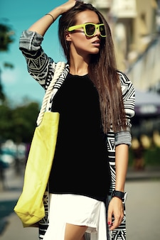 Fashion stylish beautiful young brunette woman model in summer hipster colorful casual clothes posing on street background