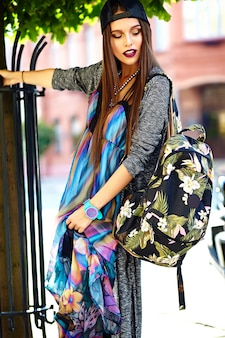 Fashion stylish beautiful young brunette woman model in summer hipster colorful casual clothes posing on street