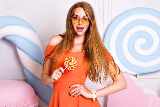 거대한 얼굴 단맛, 사탕 가게, 유행 드레스 재미있는 선글라스, 긍정적 인 분위기 근처 포즈 놀라운 금발 여자의 패션 세련된 귀여운 초상화.