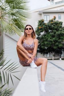 Moda donna europea abbronzata vestibilità elegante in occhiali da sole, canotta leopardata e pantaloncini da motociclista, fuori dalla villa vicino alla palma